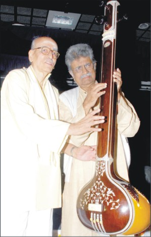 Pt. Rajeev Taranath and Pt. Indudhar Nirodi seen strumming the tamboori together to inaugurate the concert at JSS Women's College in city this morning.