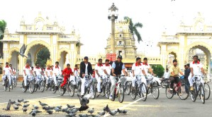Dr. C.G. Betsurmath, Commissioner, Department of Archaeology, Museums and Heritage, is seen leading a team of postal trainees in front of Kote Anjaneya Swamy Temple during the Heritage Cycle Rally which began from Town Hall premises here yesterday morning.