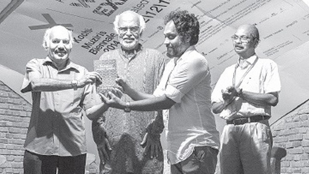 Writer Sethu handing over 'Virali Pattu, Valampiri Shankhu, Kannadi Bimbam' to Biennale director of Programmes Riyas Komu. Artist Balan Nambiar and writer-journalist Jose Panachippuram are also seen