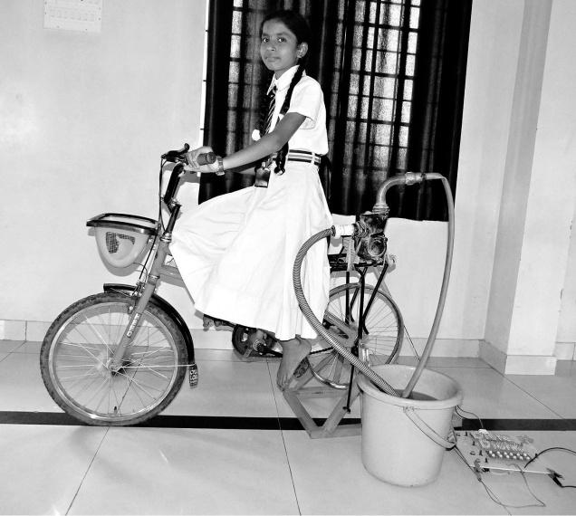 Disha Karigar demonstrating her bicycle generator.— Photo: VAIDYA