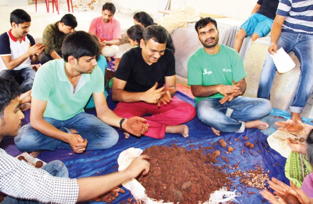 Corporate executives making seedballs using native seeds and cow dung