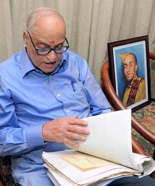 R.S. Veeraraj Urs, nephew of Naik Urs, takes a look at the postcards sent by his uncle (portrait) from the PoW camp, at his home in Bengaluru. | Photo Credit: Sudhakara Jain