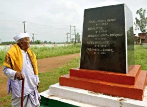 Freedom fighter N.S. Huchrayappa near the pillar erected on the outskirts of Esur with the names of freedom fighters who were hanged engraved on it.   | Photo Credit: VAIDYA;VAIDYA - VAIDYA